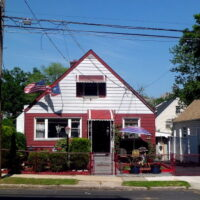 This is an image of a Baychester House With American and Puerto Rican Flags