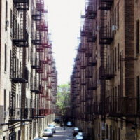 This is an image of Pelham Parkway Parking Alley Between Apartment Buildings