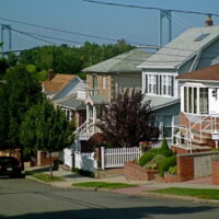 This is an image of Whitestone Houses With Bronx-Whitestone Bridge in the Background