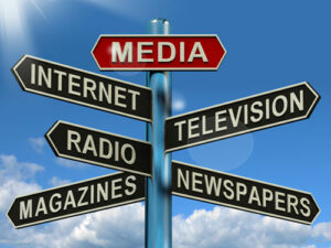 This is an image of a sign post with various types of Media pointing in different directions
