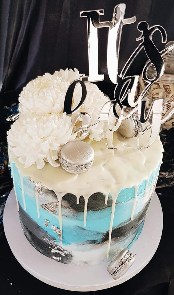 Single tier custom cake, white, blue and black icing with a white drip and white flowers.