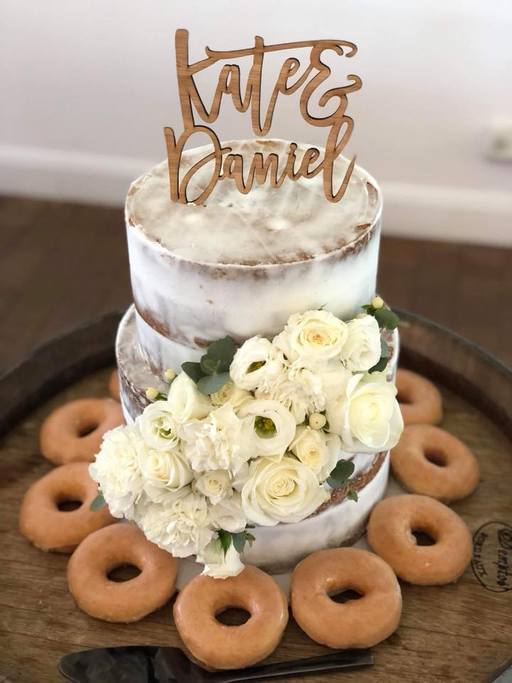 Two tier custom naked cake, white florals and glazed doughnuts.
