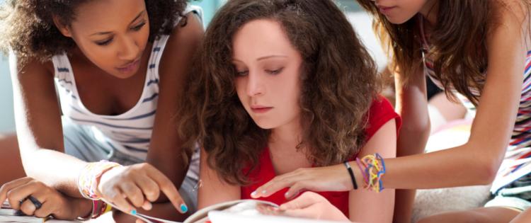 Three teen girls looking at a fashion magazine