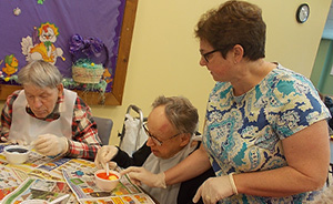 a worker assisting a resident with a painting project.