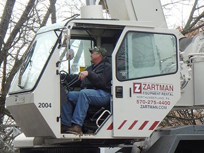 Crane operator Andrew Switzer works one of the team