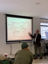 Dr. Robert Corrigan pointing to a diagram of a Norway rat burrow.