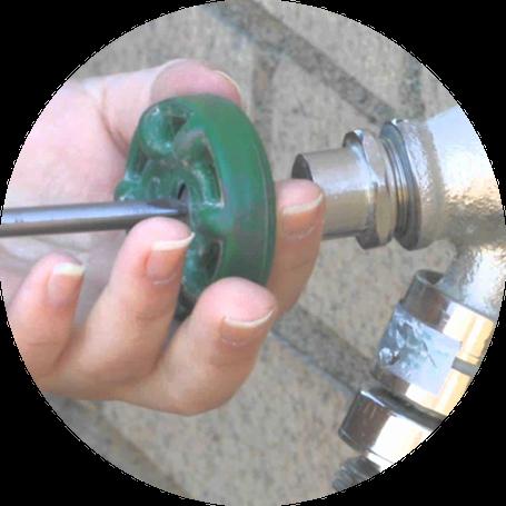 Plumber fixing an outdoor water tap