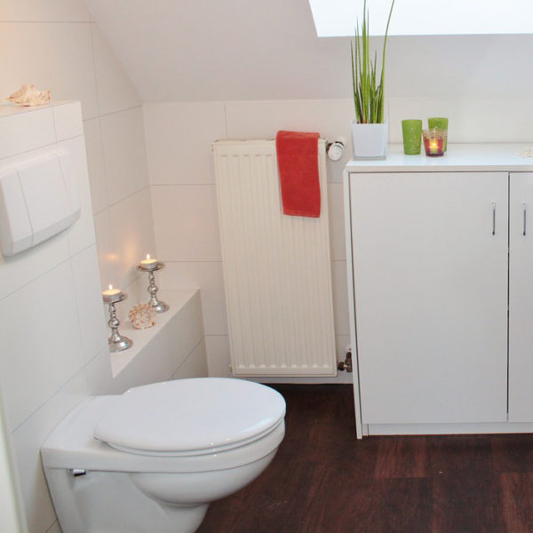 All white bathroom with toilet, candles and bright green and red decor