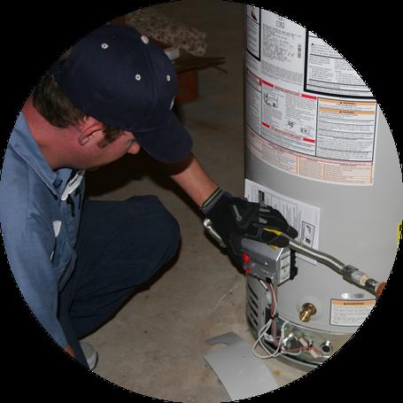 Plumber kneeling to fix a water heater