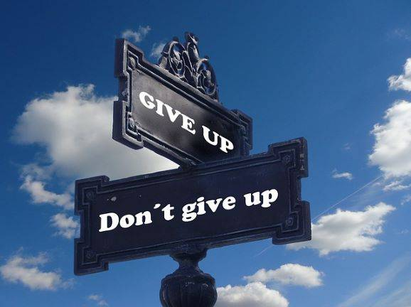 directional sign: give up, don't give up. performance based believers worship futility/end of the futility gods