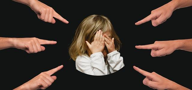 child covering her face and 6 fingers pointing out her shame