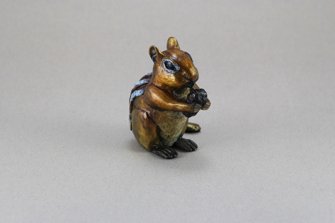Little bronze Chipmunk eating a peanut.