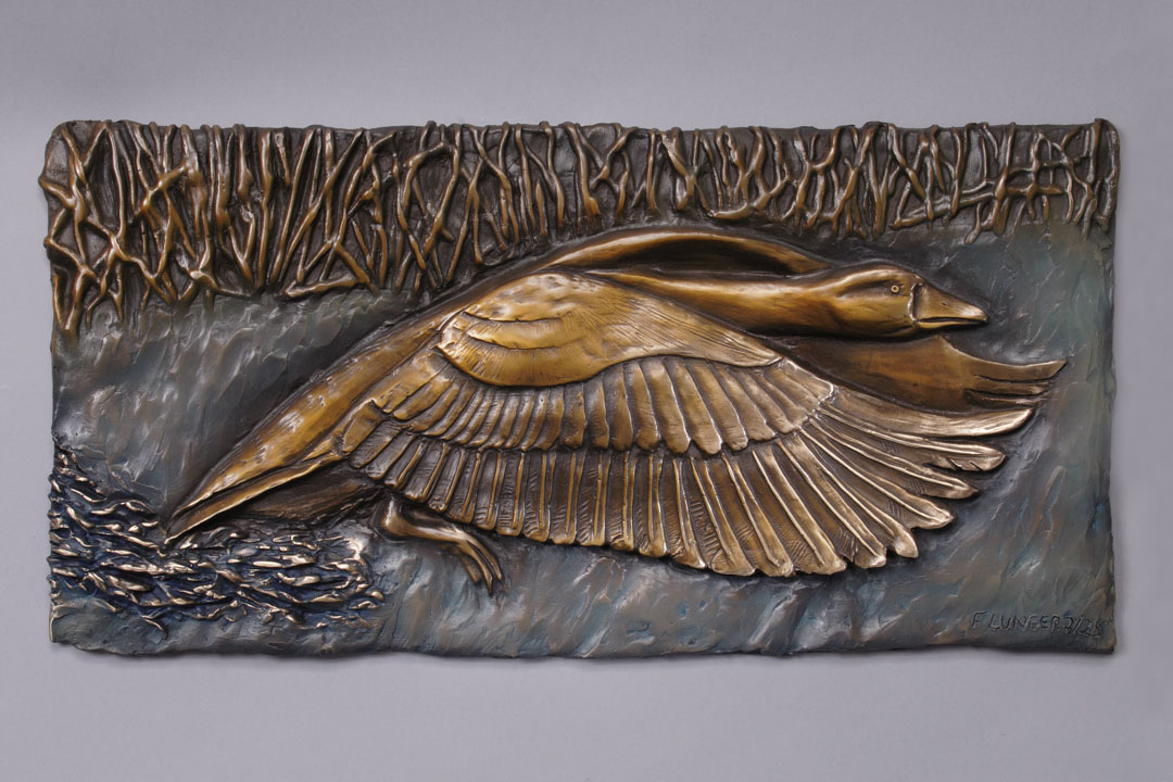 A bronze relief of a Goose taking flight