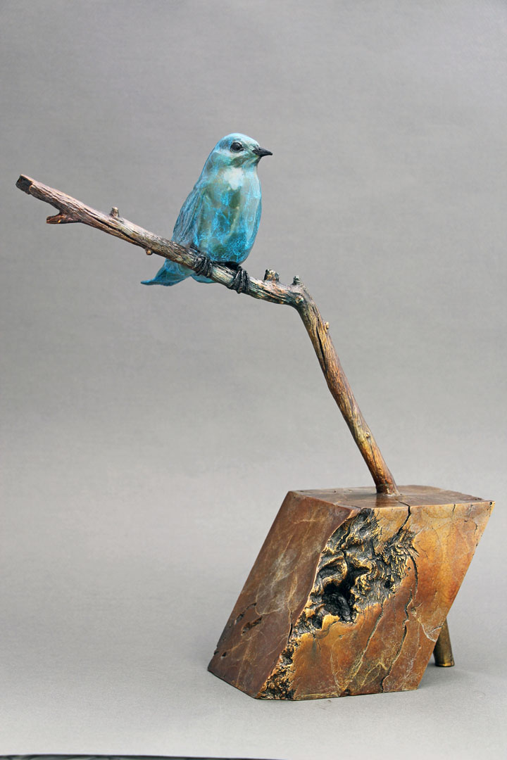 This bronze sculpture depicts a Bluebird sitting on a branch. The base was formed from the burl of a piece of scrub oak