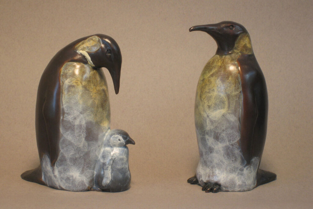 A pair of Penguins sitting with it's chick