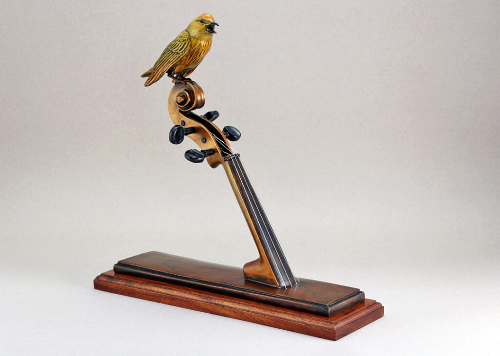 Yellow Warbler sitting atop a violin neck. Both the violin neck and Warbler are life size