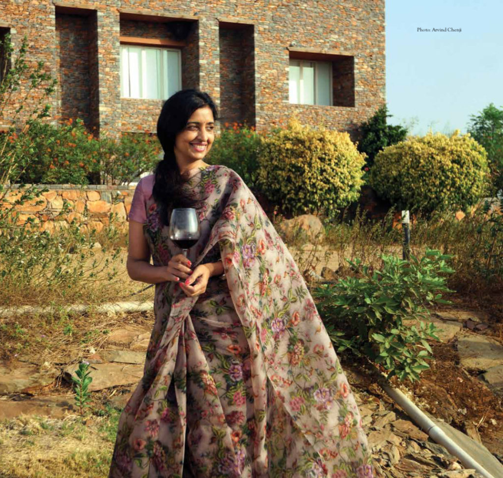 Uma poses with a glass of wine in front of the wInery at Hampi