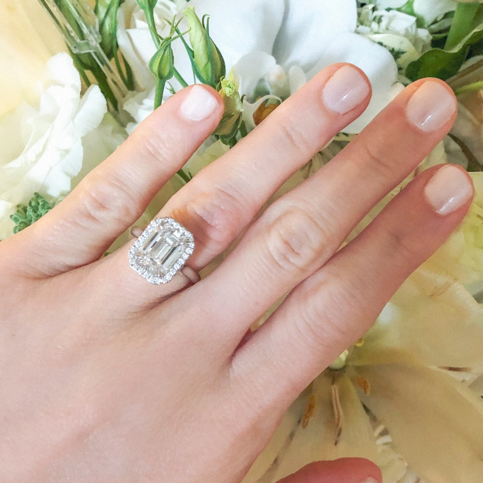 Melanie Rahaminov's engagement ring, made by her family's firm: A 2.90 ct. G-color, VS1-clarity elongated emerald cut with a double-sided halo in 18k white gold.