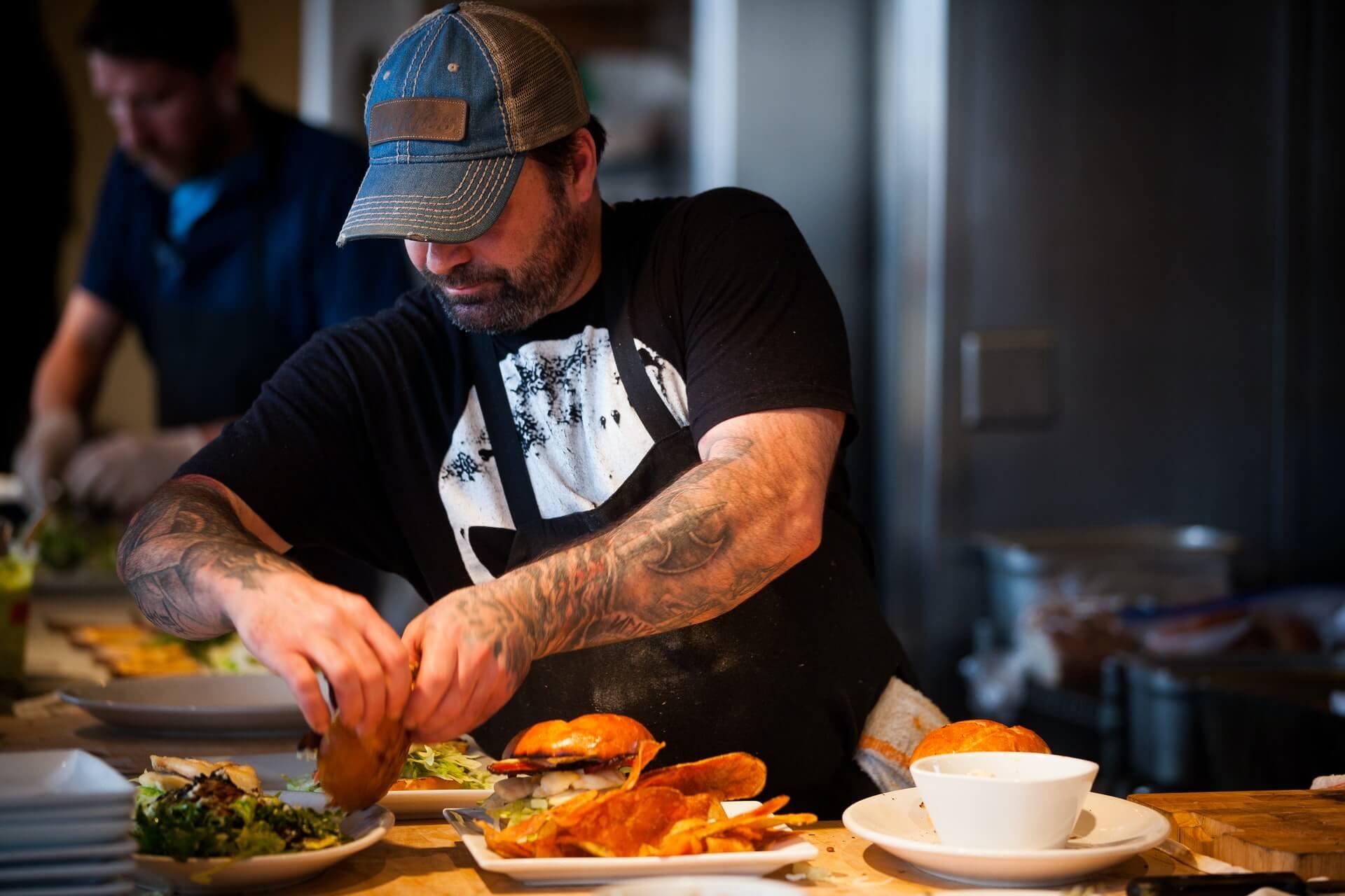 Chef preparing burgers inside restaurant