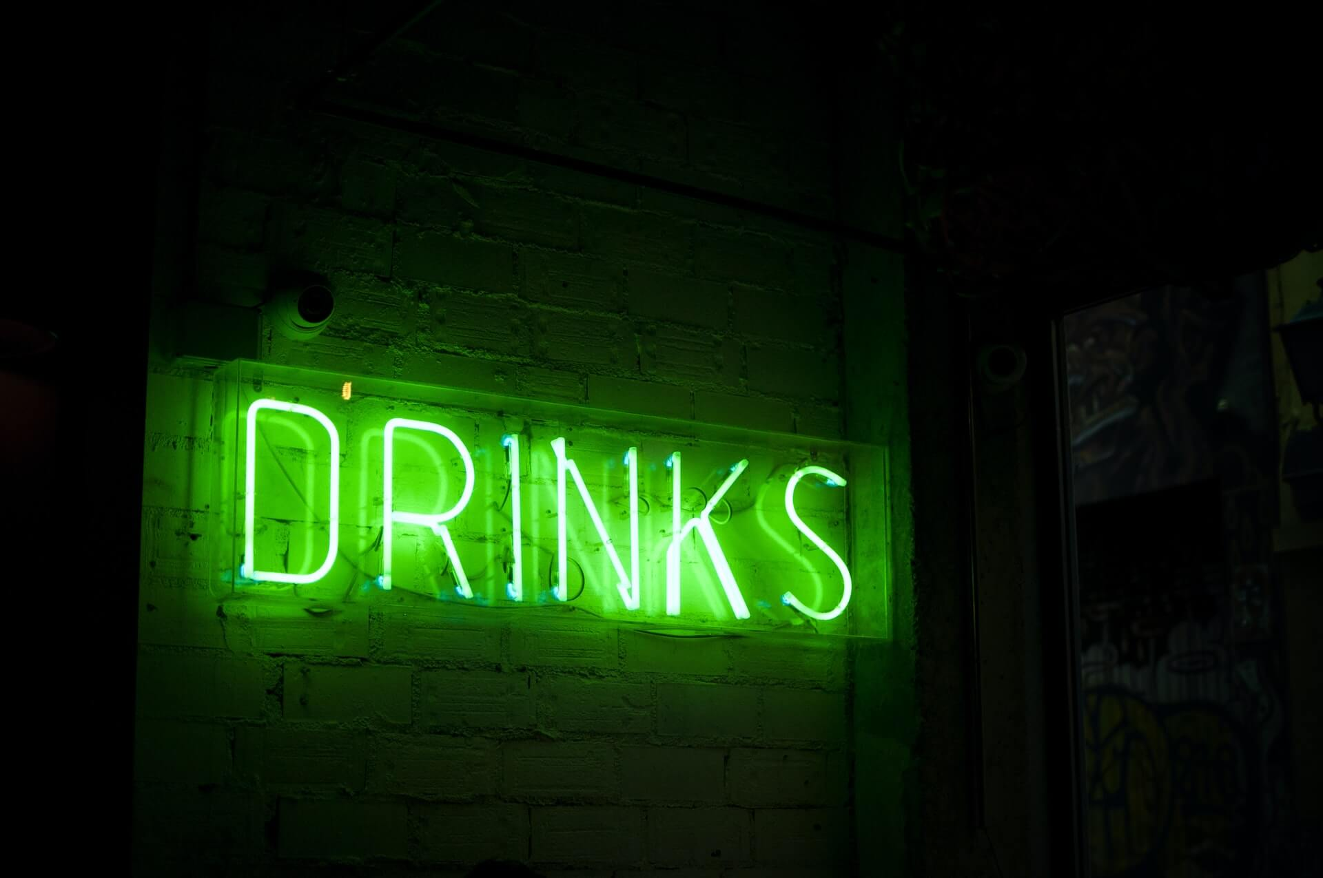 """Green neon """"DRINKS"""" sign on brick wall"""