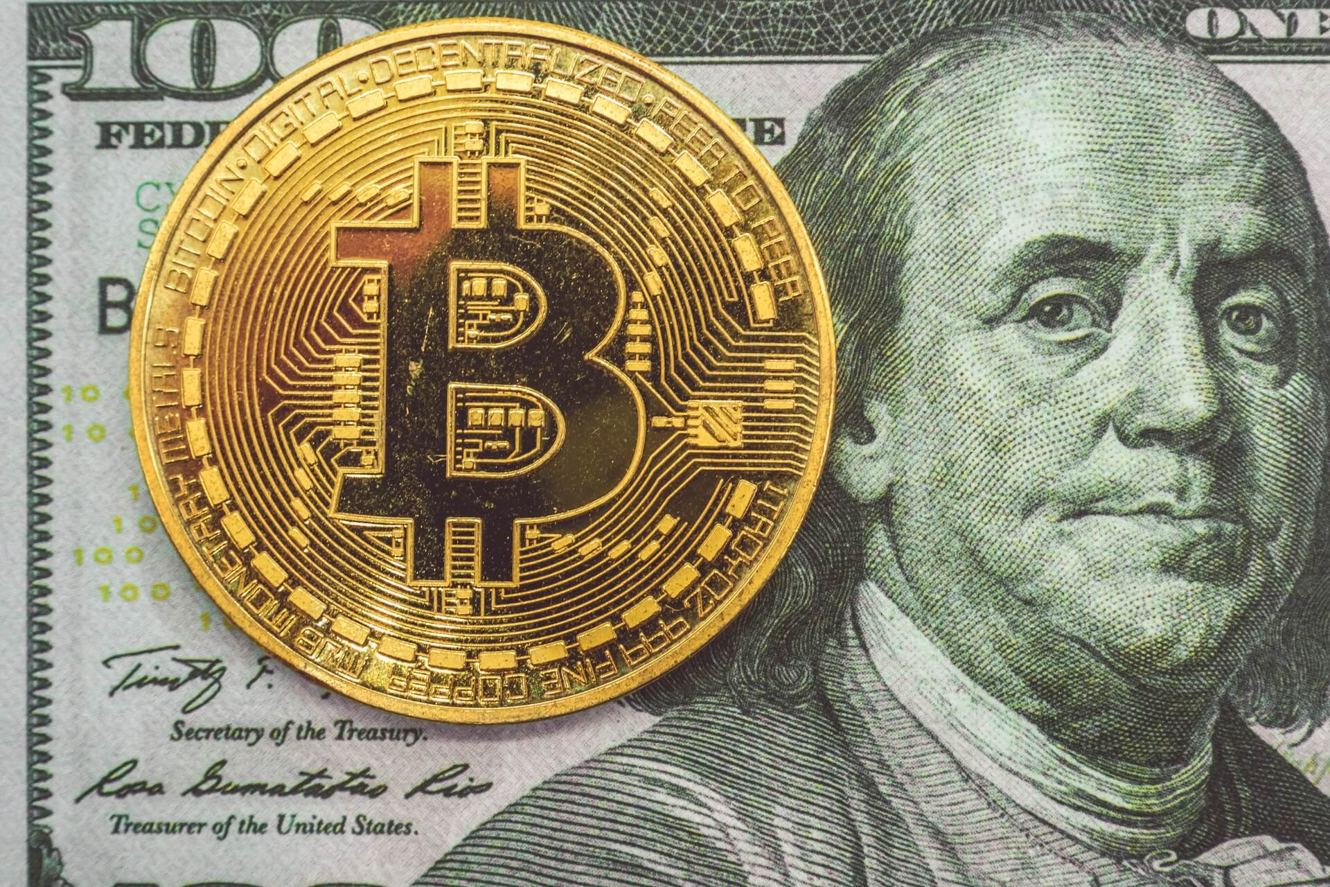 A Bitcoin on top of a $100 bill