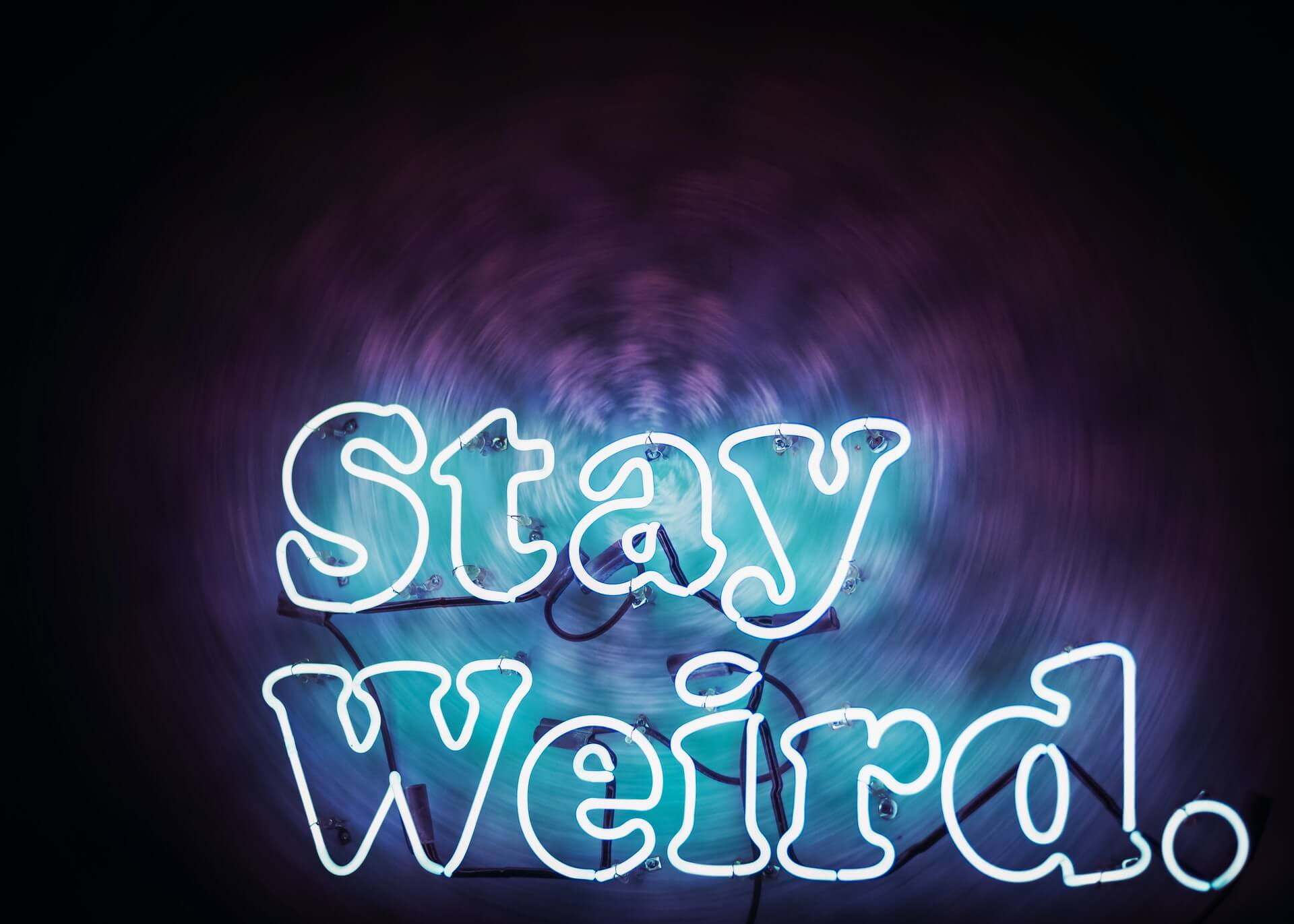 Stay Weird neon sign with purple background