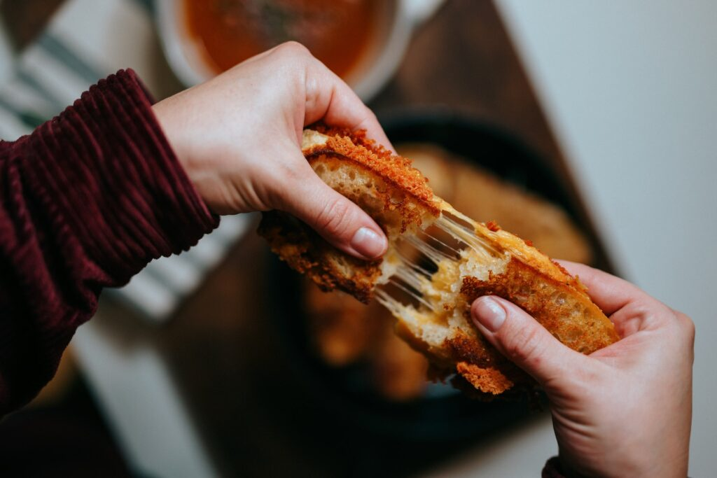 Person pulling apart melty grilled cheese sandwich