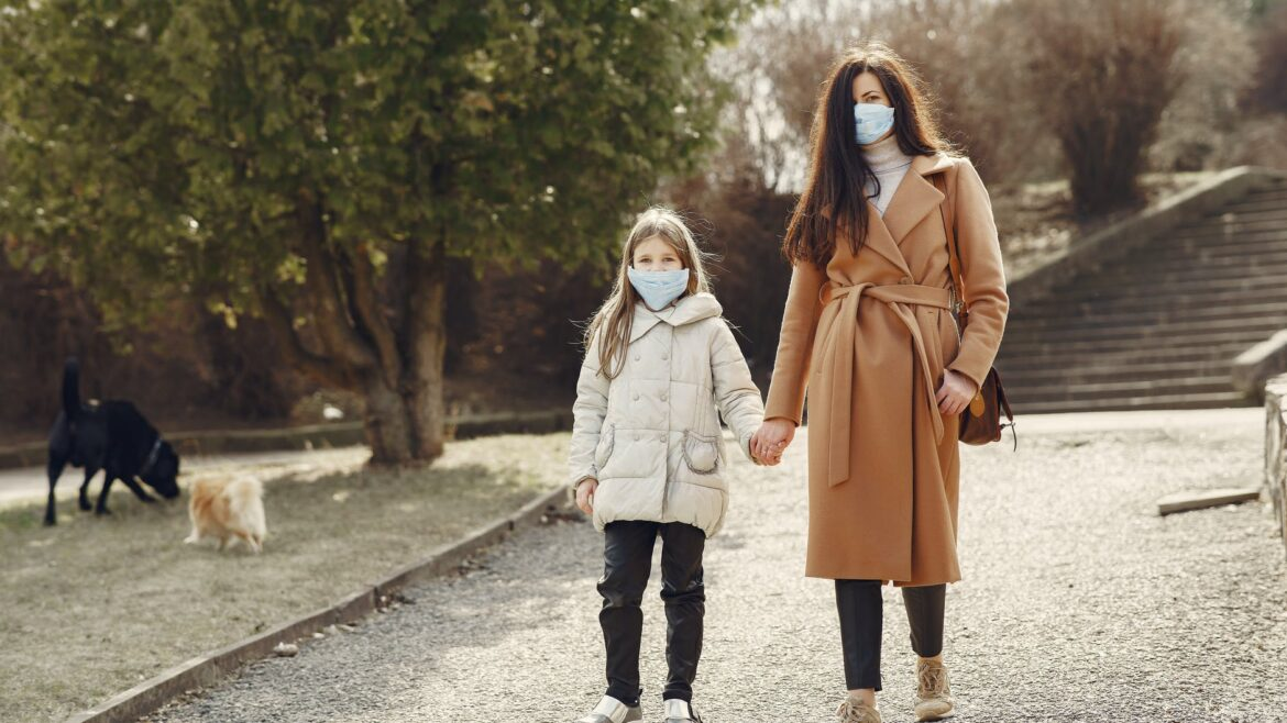Masked mom and daughter in park
