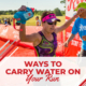 Female triathlete crosses the Rookie Triathlon finish line with her hands raised in the air. Text on design reads Ways to Carry Water on Your Run. Learn more at https://therookietri.com/carry-hydration/