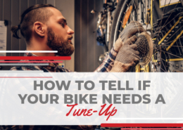 Man works on the chain at the rear of a bike in a bike shop. Text on designs reads How to Tell If Your Bike Needs a Tune-Up. Learn more at https://therookietri.com/tune-up-your-bike/