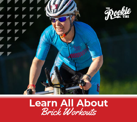 Female cyclist rides her bike in a blue kit with a big smile on her face. Text on design reads Learn All About Brick Workouts. Learn more at https://therookietri.com/learn-about-brick-workouts/