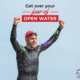 Triathlete exits the water in his wetsuit after a swim with his arms raised in the air. He's smiling after completing the swim. Text on design reads Get Over Your Fear of Open Water. Read more at https://therookietri.com/fear-of-open-water/