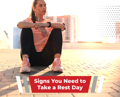 Female triathlete sits on the ground to rest after a run. Text on design reads Signs You Need to Take a Rest Day. Read more about the importance of rest days at https://therookietri.com/importance-of-rest-days/