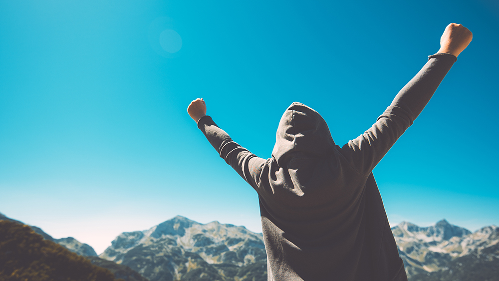 Man on top of mountain holding hands up in victory.