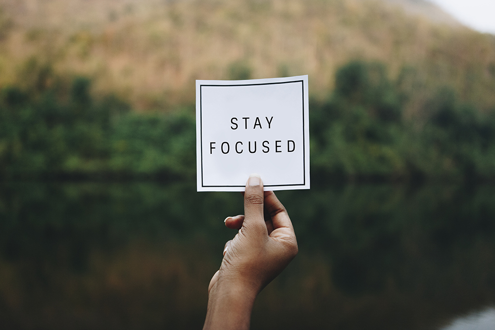 Hand holding piece of paper that says stay focussed