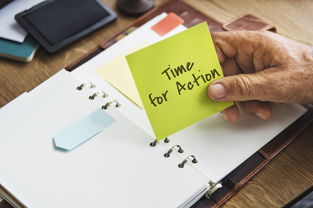 Post it note that says time for action in diary