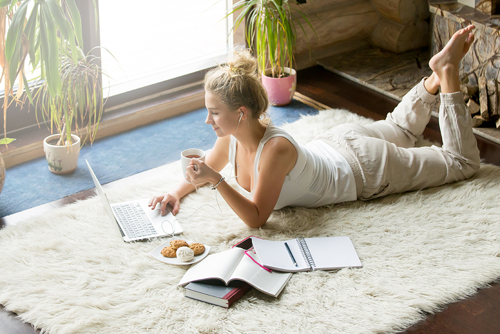 Women laying on floor doing work and sipping coffee