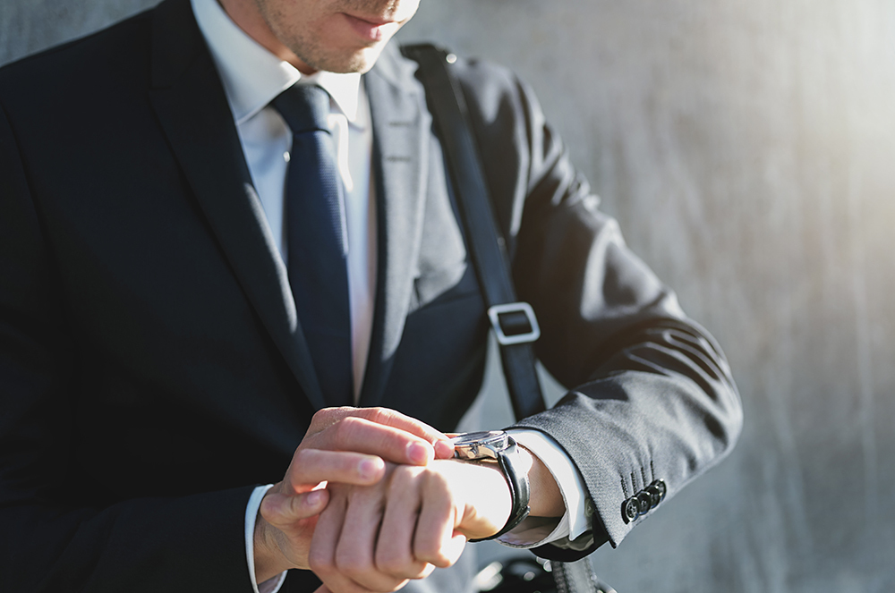 Business man in suit looking at watch