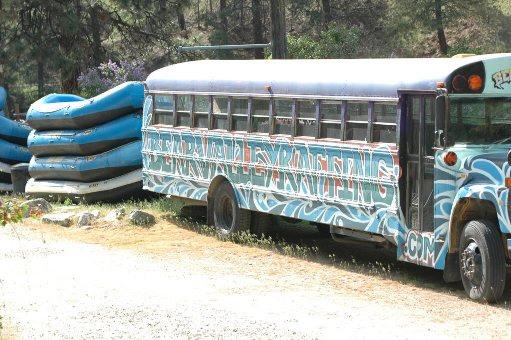 Blue whitewater rafting boats, and bus