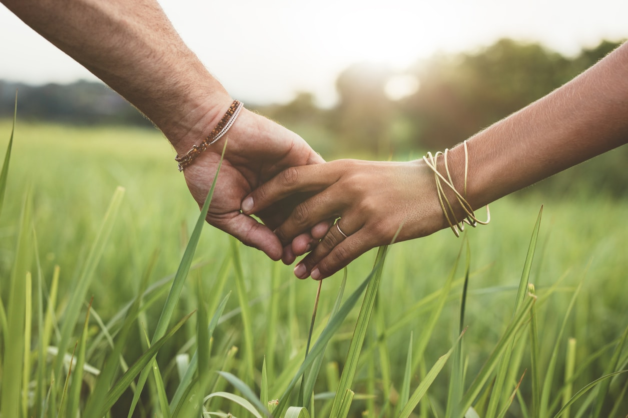 man holding woman's hand while walking in the grass