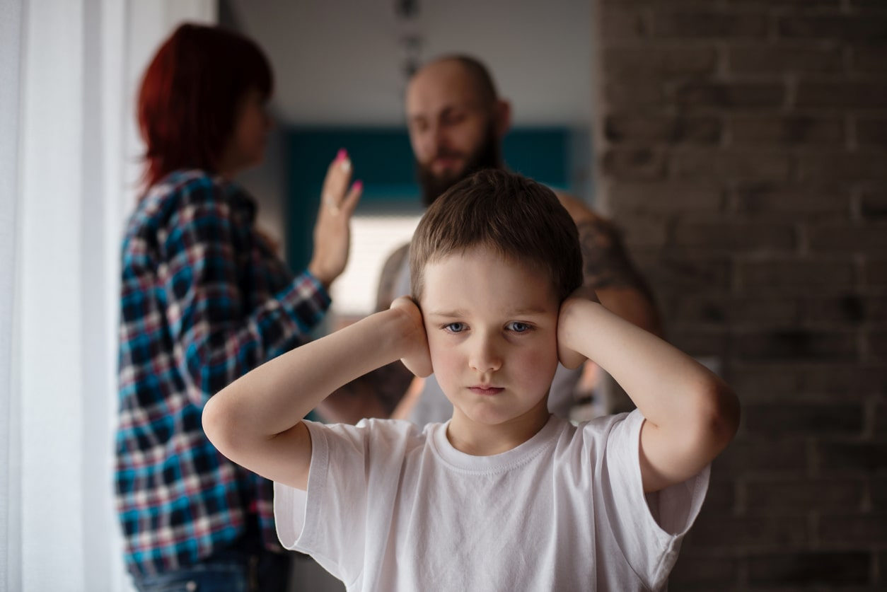boy covering his ears as couple fights