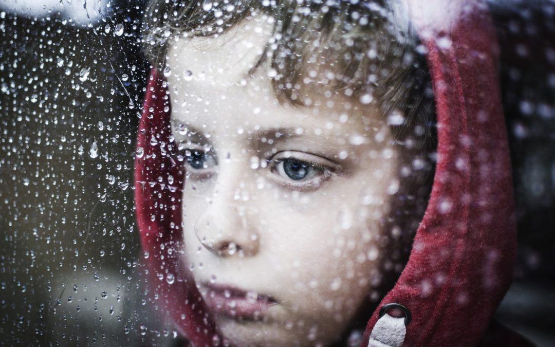Traumatized little boy looking out window