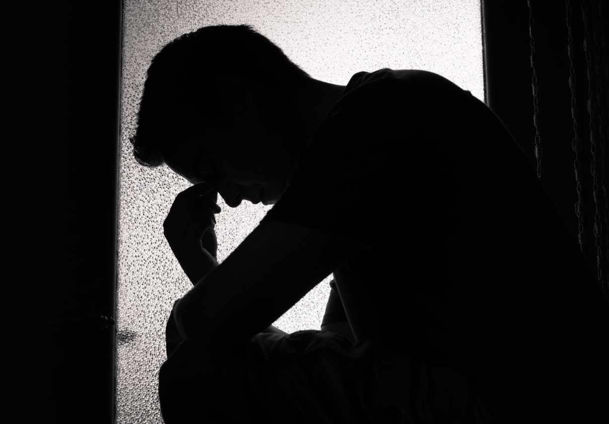 Depressed man sitting in window