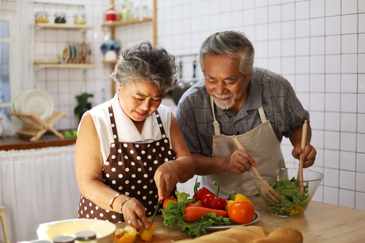 Happy Asian American Couple cooking together