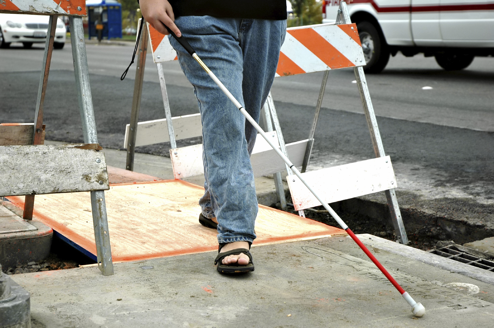A man uses a white cane to navigates through construction on a sidewalk