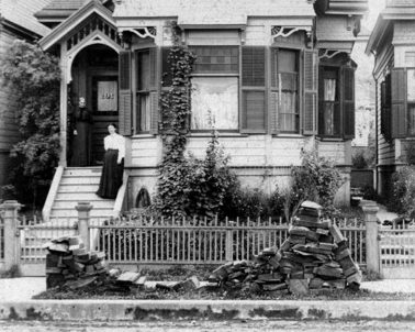 Image of a partly depleted slab wood pile in front of a home along the sidewalk in late 1890s. Women is standing on the stairs leading into her home.