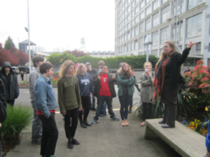 Group of high school age students on Slabtown walking tour. Tanya is standing on a bench ponying at Montgomery Park (once a Montgomery Ward regional center and department store currently the second largest office building in Portland).