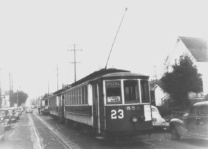 "Line of three street cars headed to Vaughn Street Ballpark. Signs in the front street car #23 Special ""TO BALL GAME""-there are some sweet vintage 1940s looking cars parked on the street. The purpose of this image is to highlight that streetcars were a big deal in Slabtown."