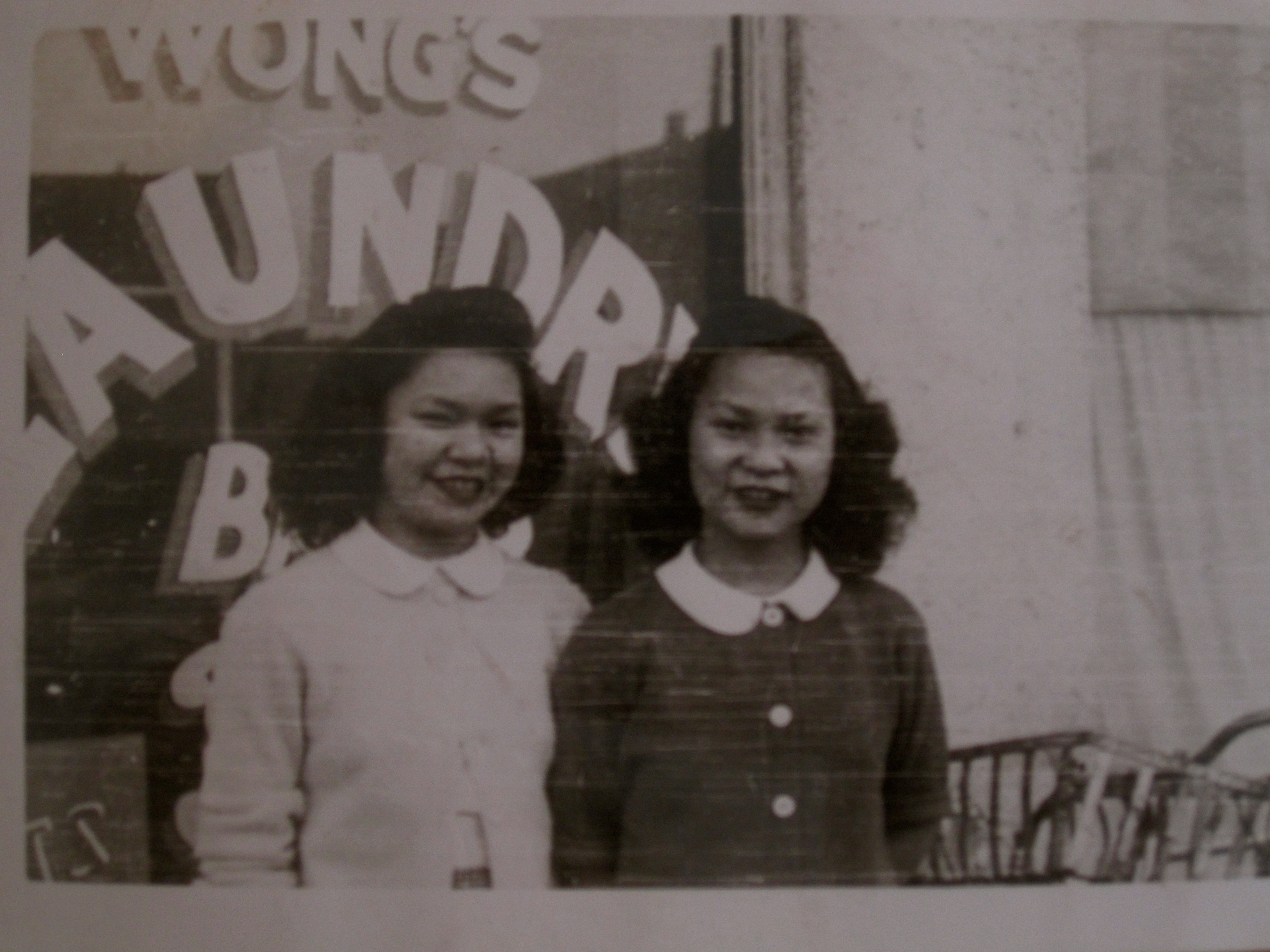 Two young sisters in front of family laundry.