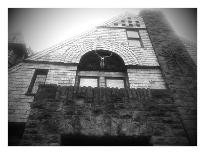 Black and White exterior image of a stone house with a stage head under an archway. A very unusual example of Queen Shingle Style because the shingles are made of slate. The chimney is massive with decorative metal sun on the basalt rock that starts at the basement level and then contrasts with the shingles..